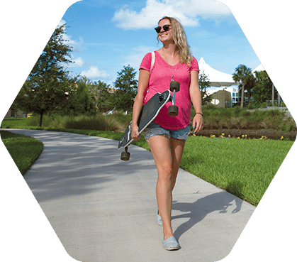 Female student carrying longboard while walking around campus