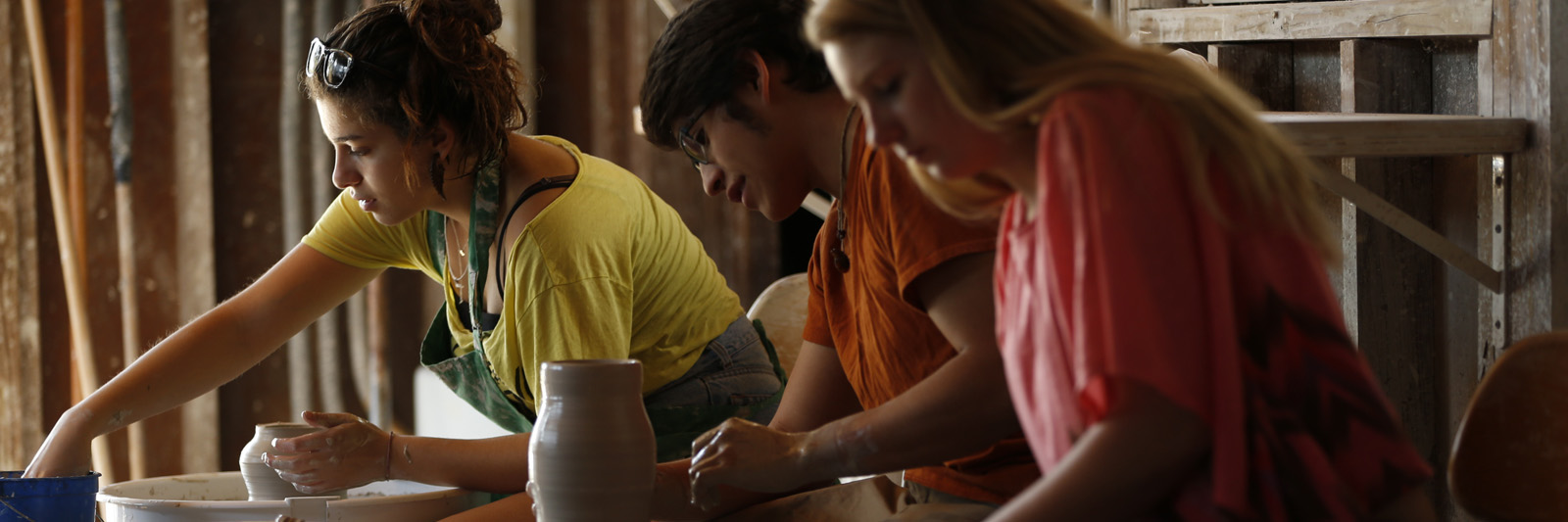 Students work with clay on a pottery wheel
