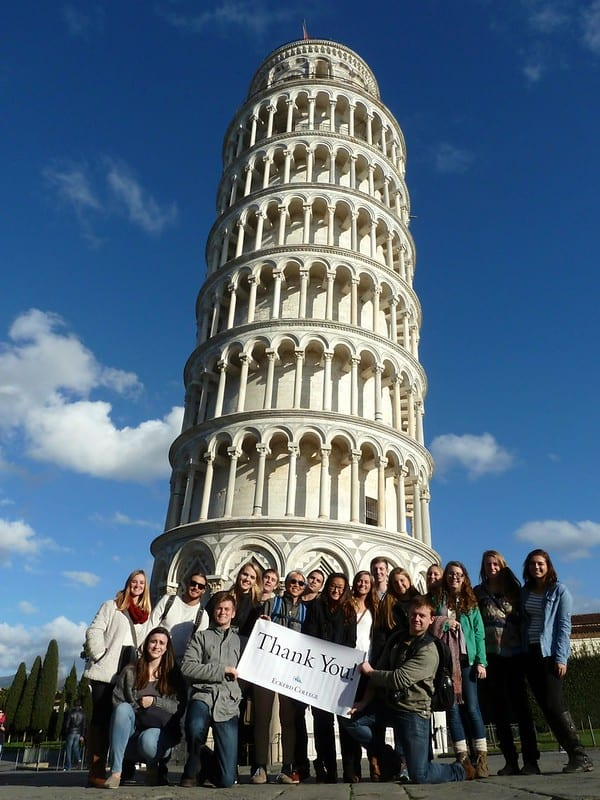 Students holding thank-you banner in front of tower of Pisa