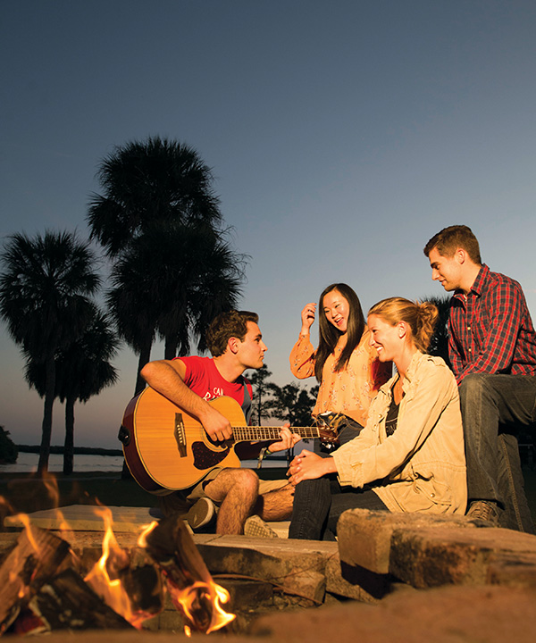 Eckerd students around a bonfire on beach with guitar in 2015