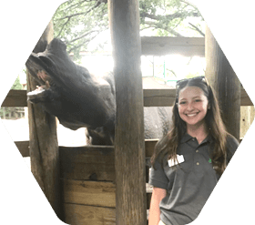 Student standing in zoo with rhino behind her
