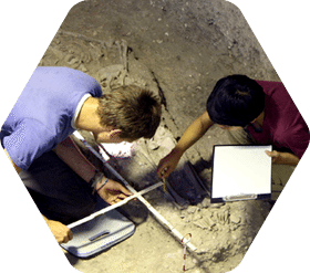 Two students excavating artifacts as part of a biological anthropology trip in Lopburi, Thailand.
