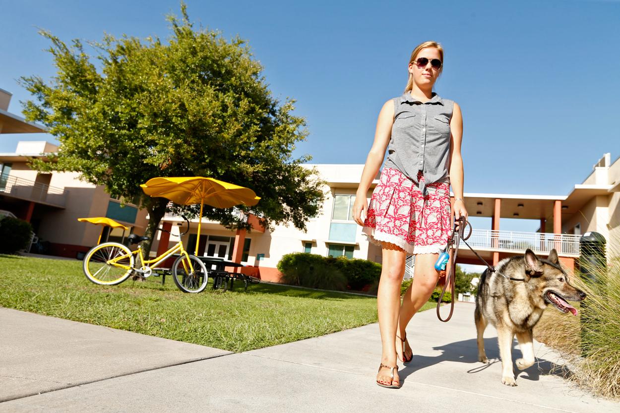 Female student walking dog outside Iota