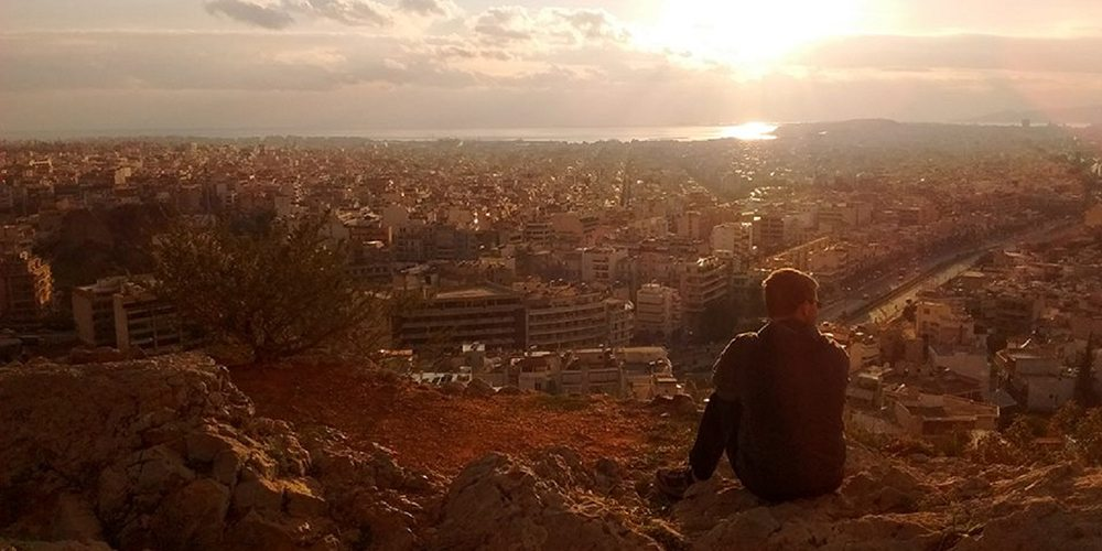 Student sitting on a cliff overlooking a city in Greece at sunset