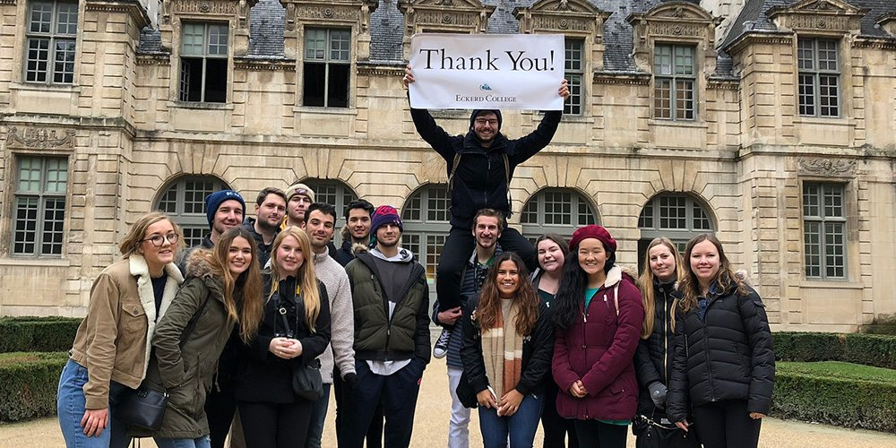 Students in front of hotel in Paris holding thank-you banner