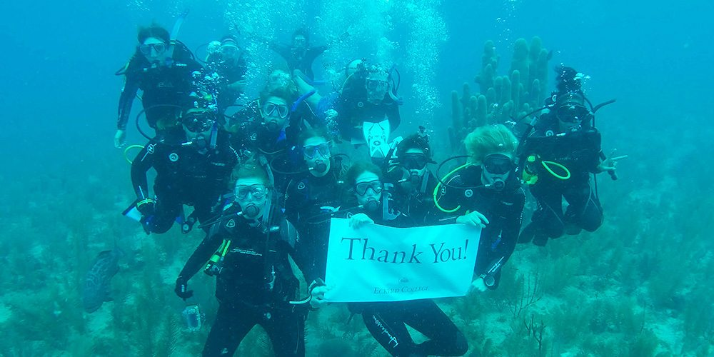 Students underwater holding thank-you sign