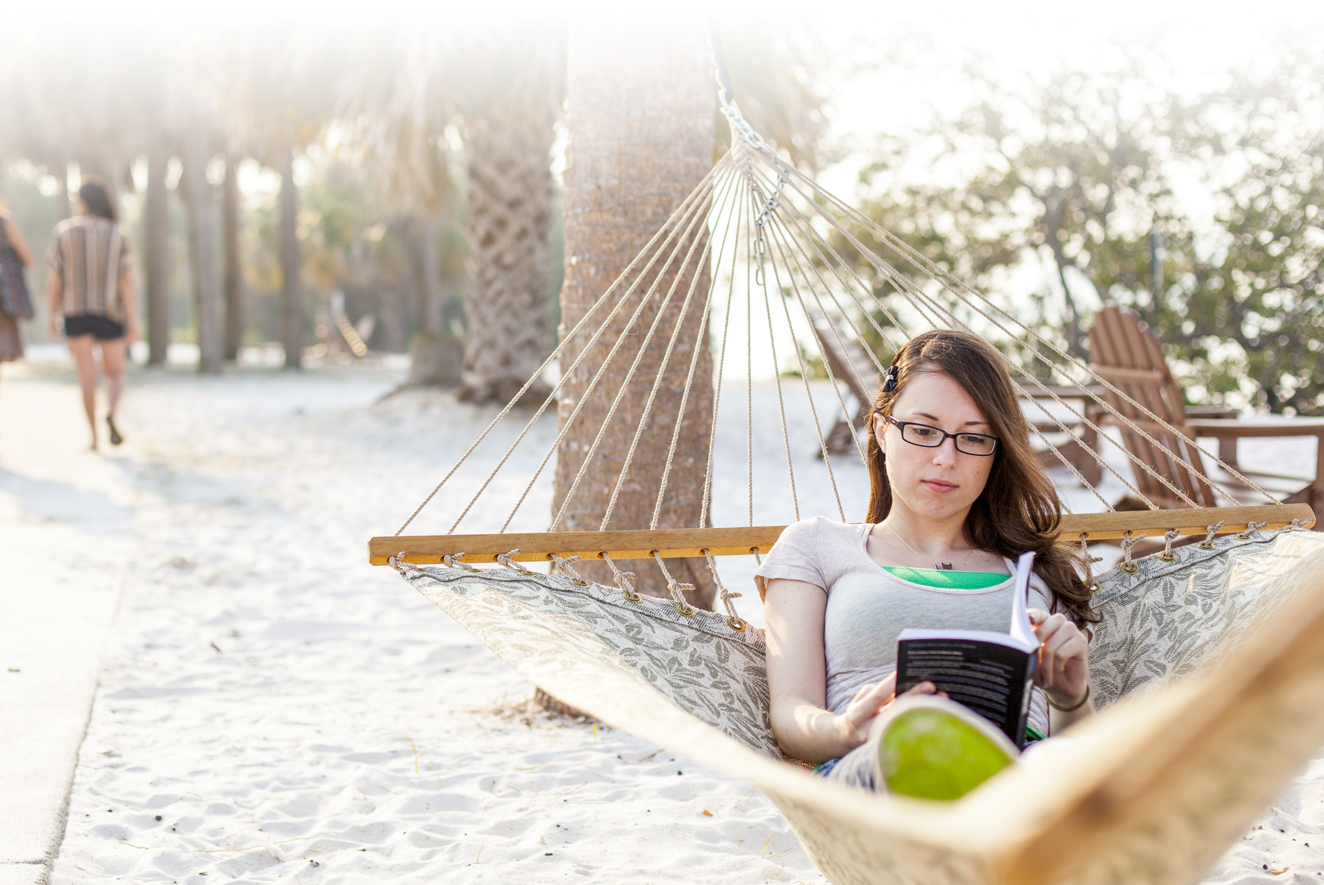 Literature degree seeking student reads a book in a hammock on Eckerd College South Beach