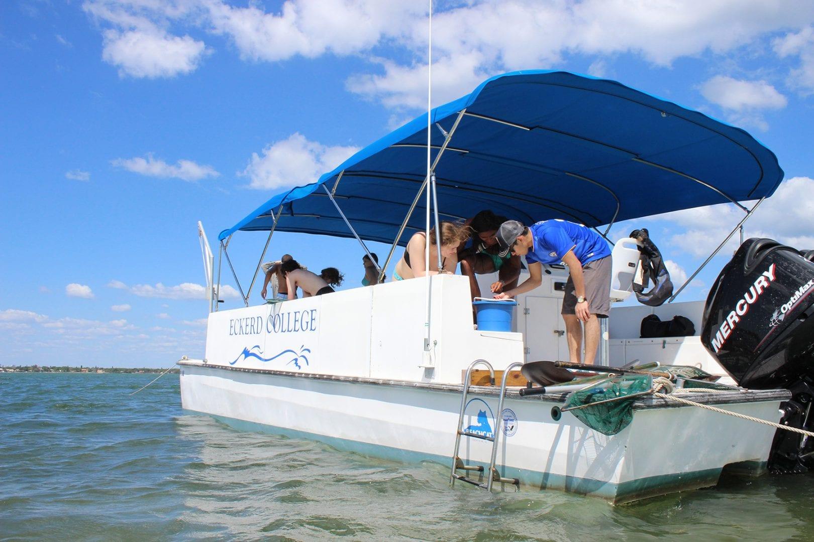 Students studying specimens aboard the Eckerd College catamaran
