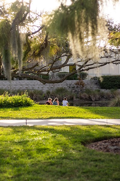 Students sitting by James Center pond