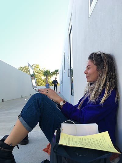 Student with laptop sitting against wall of arts center