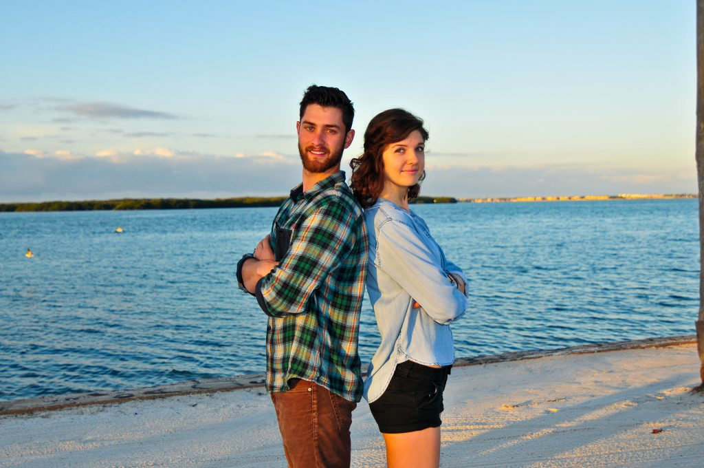Henry Ashworth and Sidney Fulford stand back to back with arms crossed on Eckerd College's South Beach.