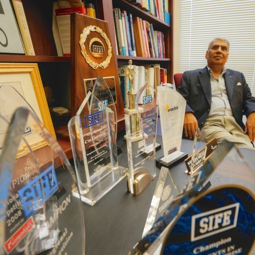 Dr. Malhotra sits in his office with numerous SIFE awards on his desk.