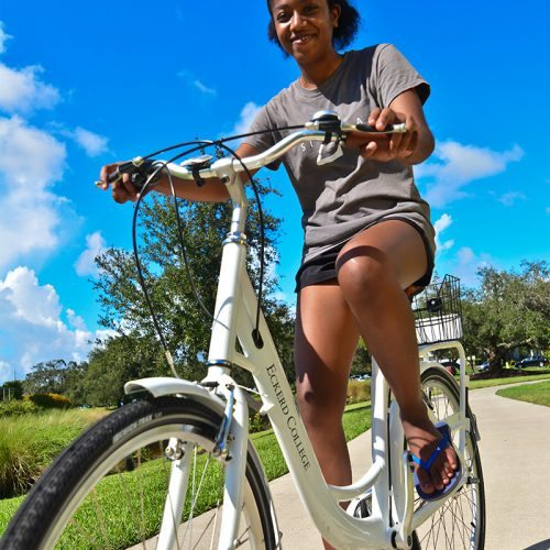 Female student rides new bicycle provided by On Bike Share for students to take off campus.