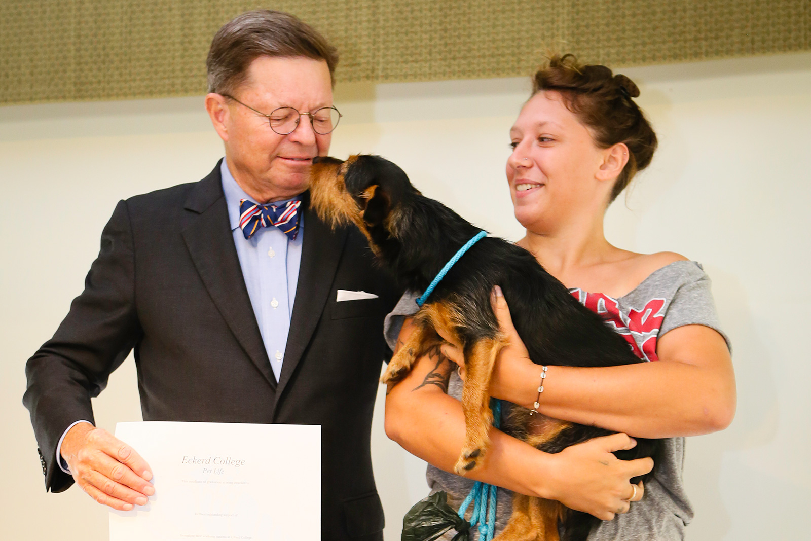 Dog licks Dr. Eastman at Pet Commencement