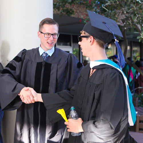 Jon Chopan shakes hands with an Eckerd College graduating senior