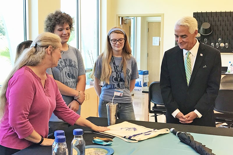 Professor Gowans shows products to U.S. Congresman Crist while students look on