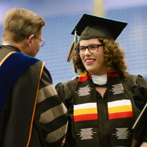 Lina Longtoe Schulmeisters '18 shaking hands with President Eastman at Commencement