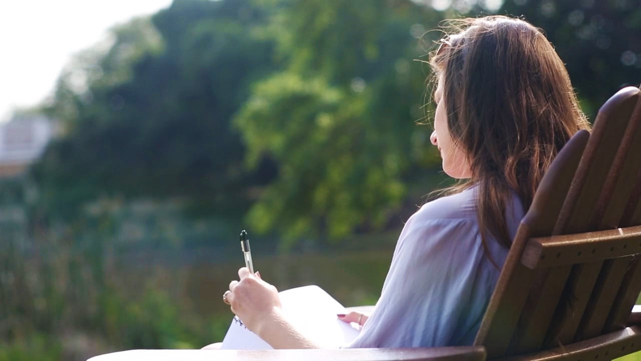 Creative Writing student writing on the beach