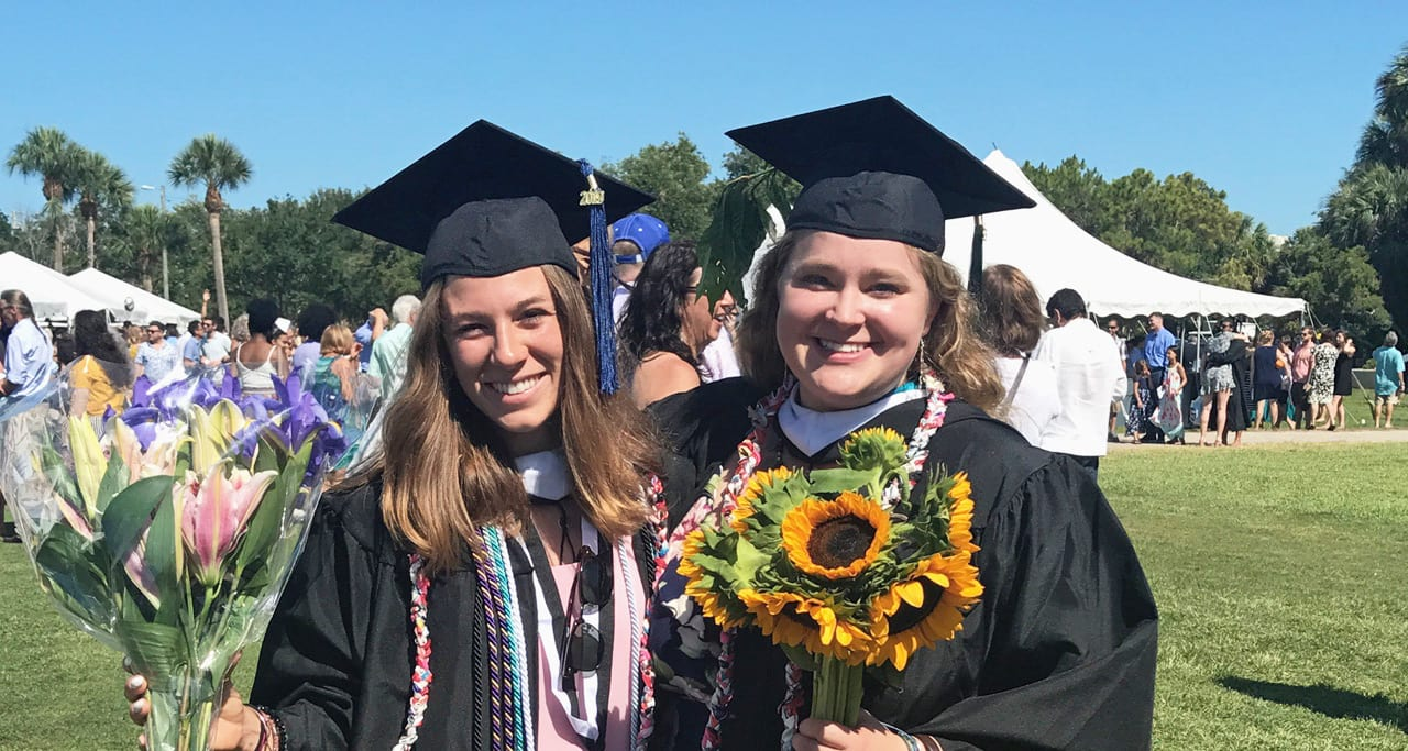 Francesca Larrain and Anna Lindquist standing with plastic honor cords at Commencement