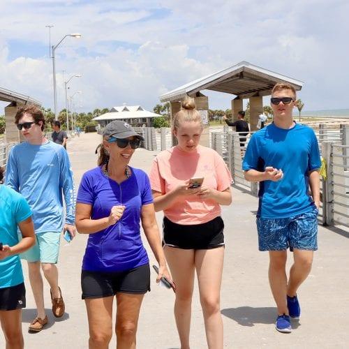 Professor Forys with students, walking along pier