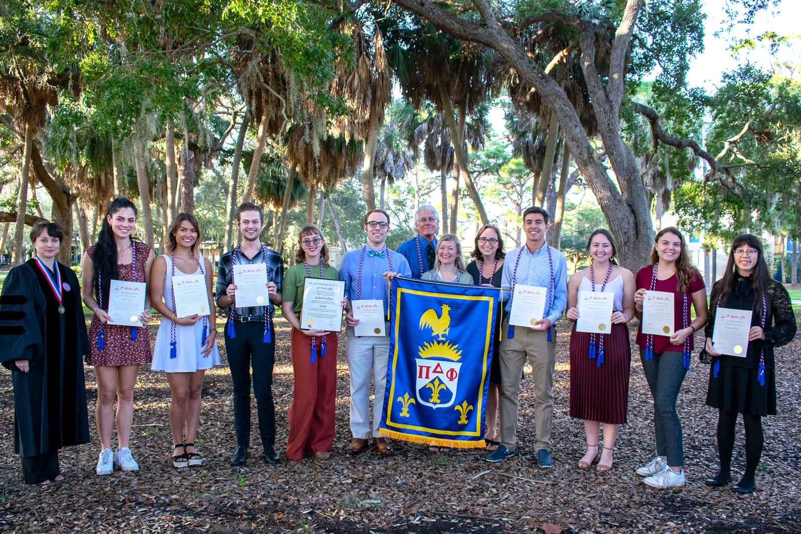 Faculty and students of Pi Delta Phi honor society standing in quad
