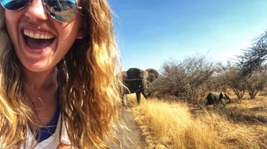 African elephants behind woman in sunglasses