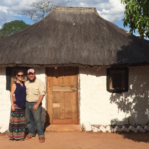Couple standing out of a simple home in Zambia