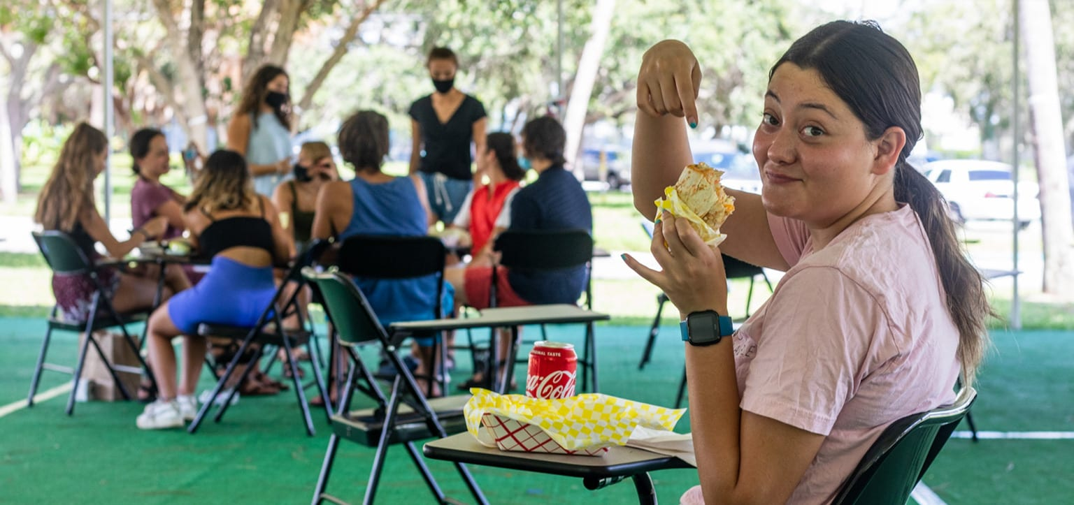 Eckerd student eating food from food truck on campus