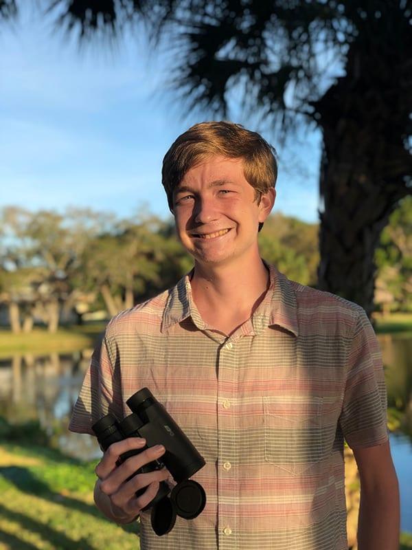 Eckerd student holding binoculars
