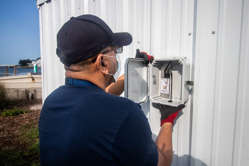 Staff installing box on side of shed