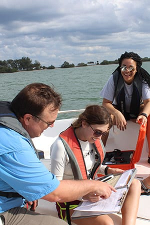 Professor on boat with Eckerd College students looking at dolphin observations