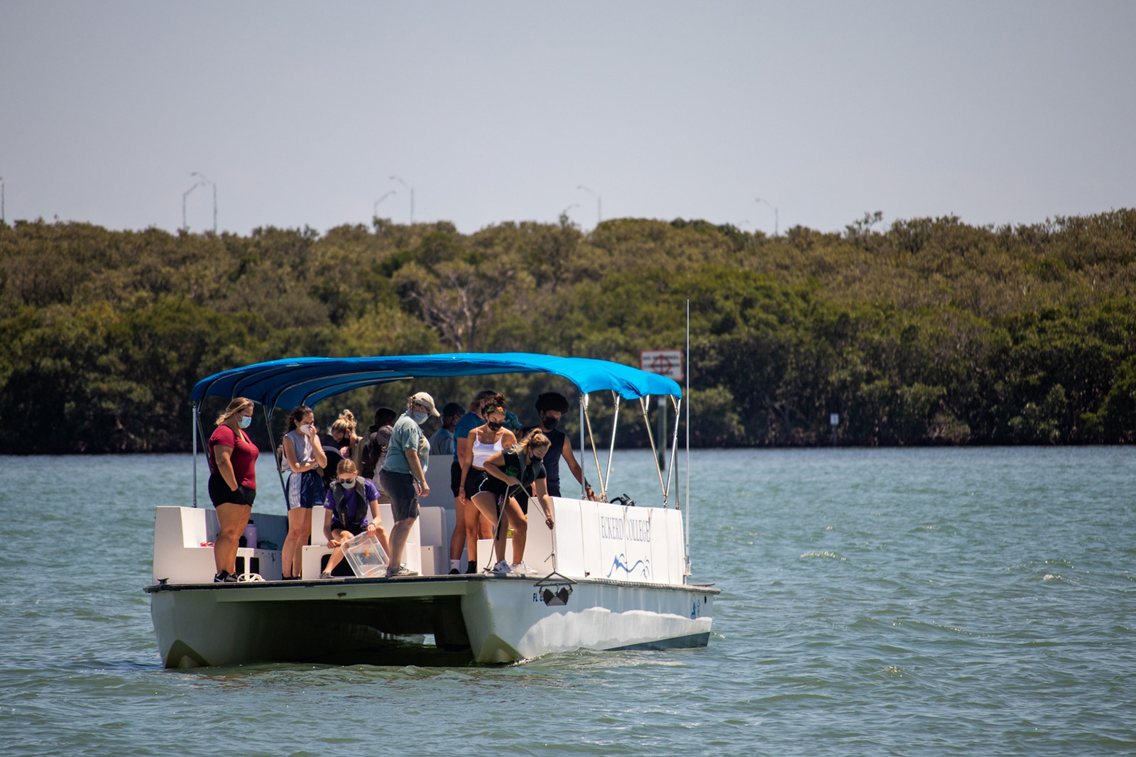 Faculty and students on a boat taking samples from seafloor