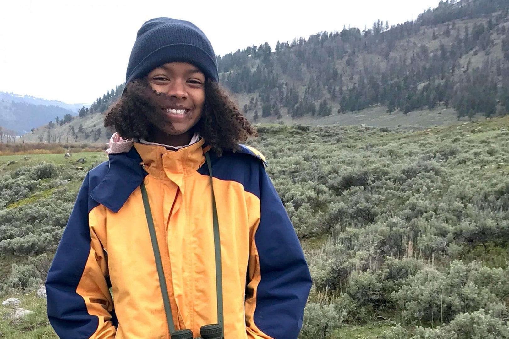 Student wearing binoculars in wilderness setting