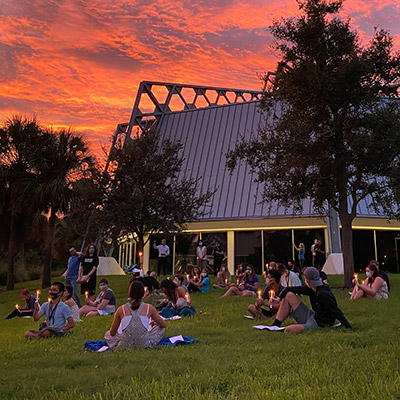 Eckerd College first-year students sit by chapel under a vibrant sunset