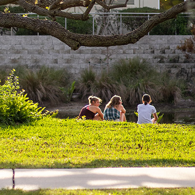 Eckerd College students seated at the edge of a pond in Florida