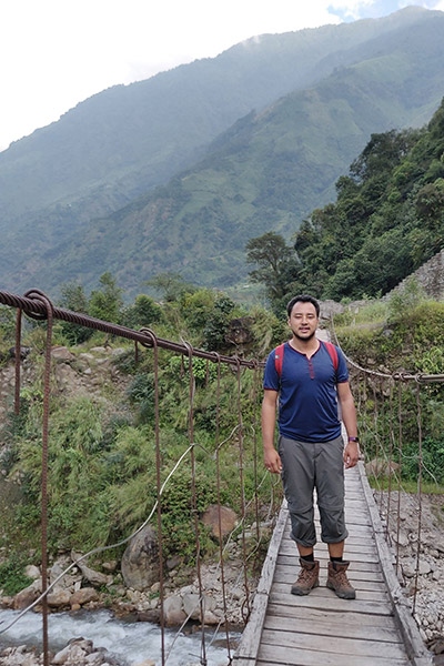 Rupak on a wooden bridge in the mountains