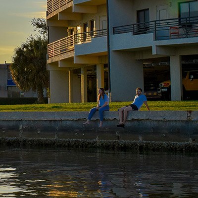 Students sit along the seawall next to the Omega residence hall at Eckerd College
