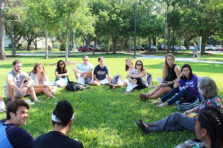 Class sitting outside in a circle with professor