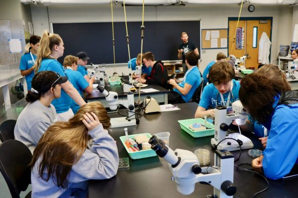 Pre-College students listening to professor in lab