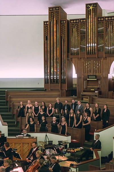 Choir singing in front of large organ