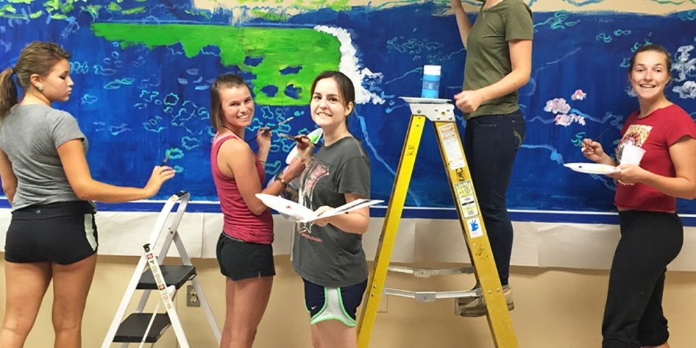 Visual arts students paint a mural for Westminster Suncoast retirement community