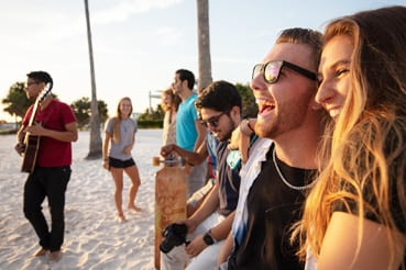 Students laughing on the beach