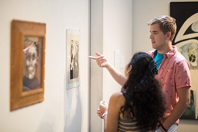 Two students discuss a piece of artwork in gallery