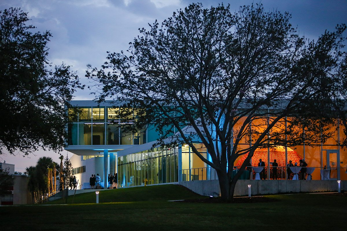 The Nielsen Center for Visual Arts viewed at night with exhibition in gallery visible