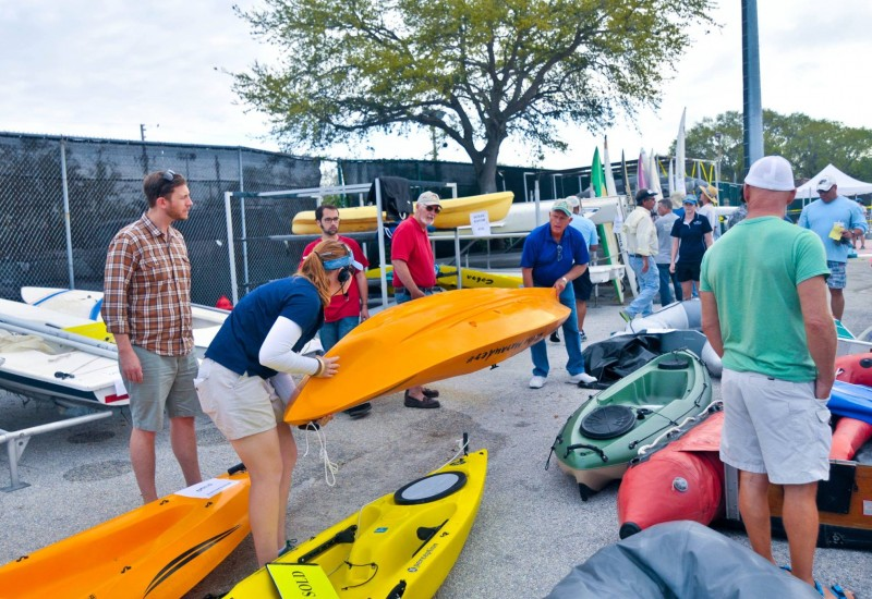 EC-SAR member helping a customer lift a kayak at the Marine Yard Sale