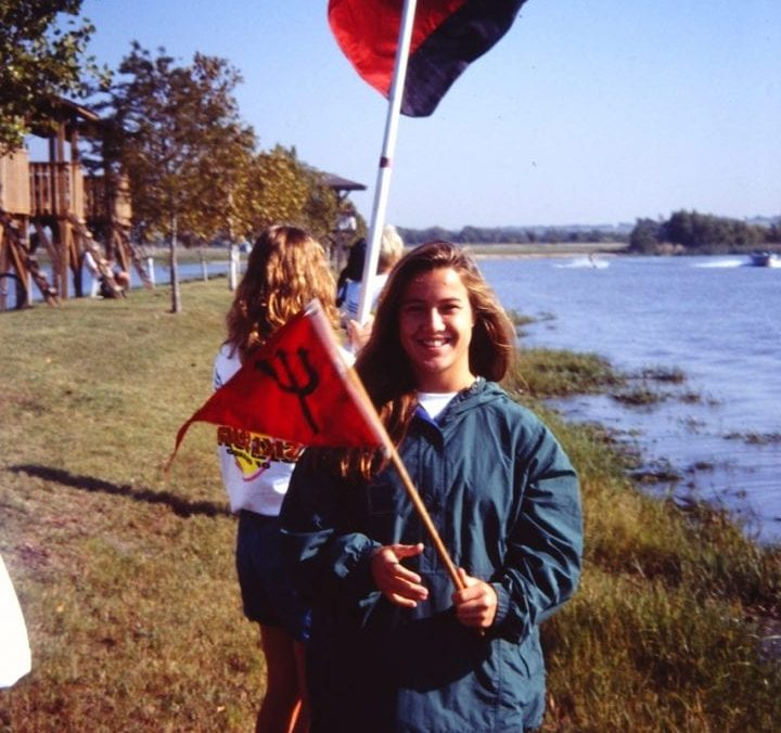 Student holding flag along water