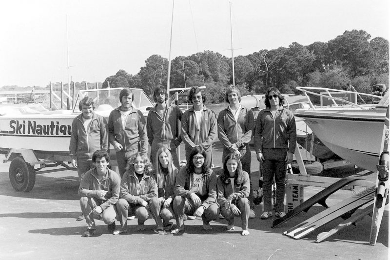 Black and white photo of students posing in front of boat