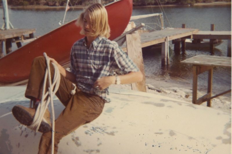 Old photo of student in bell bottoms tying a rope