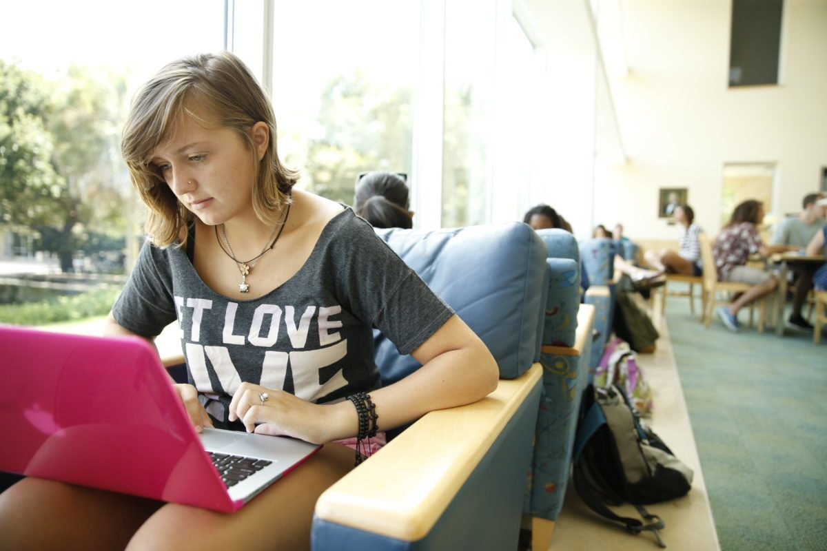Female student looking at her laptop in the library