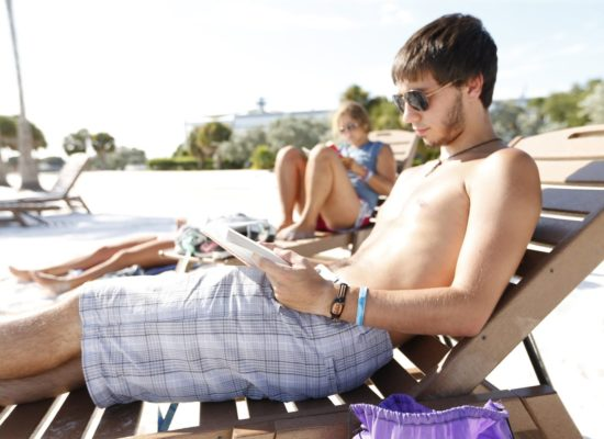 Male student reading in a lounge chair at South Beach